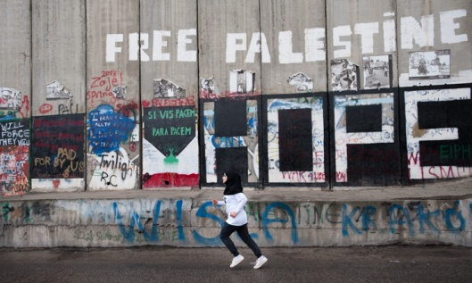 "A young woman runs past the slogans ""Free Palestine"" and ""Hope"" painted on the Israeli separation wall as hundreds of Palestinian and international athletes took part in the the inaugural Palestine Marathon which took place in Bethlehem, West Bank, April 21, 2013. Under the title ""Right to Movement"", runners had to complete two laps of the same route, as organizers were unable to find a single course of 42 uninterrupted kilometers under Palestinian Authority control."